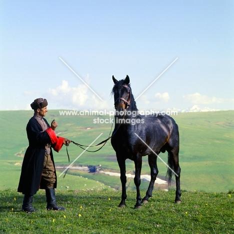 Arbich, Kabardine stallion held by cossack in Caucasus mountains