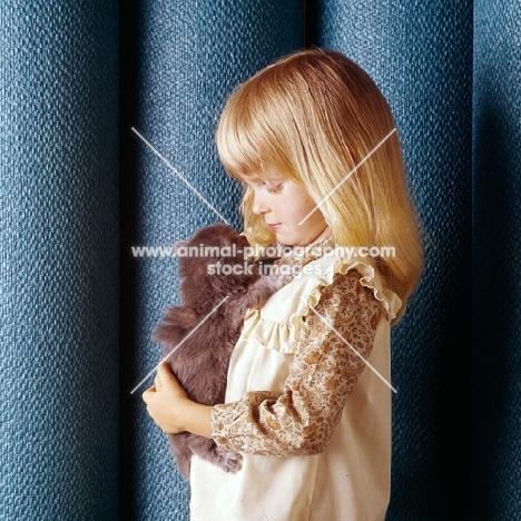child holding Persian tortoiseshell kitten