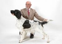 Picture of man posing his champion Large Munsterlander